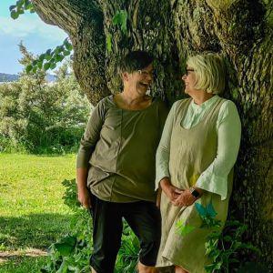Två kvinnor står under en gammal stor lind.