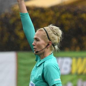 Fotbollsdomaren Lina Lehtovaara visar ett gult kort.