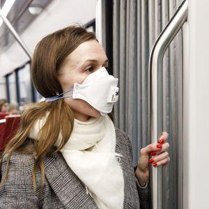 En kvinna bär munskydd i spårvagnen.