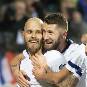 Suomen miesten jalkapallomaajoukkueen pelaajat halaavat.