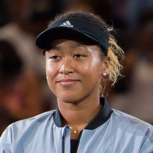 Naomi Osaka och Serena Williams står på varsin sida om tennisnätet bredvid varandra.