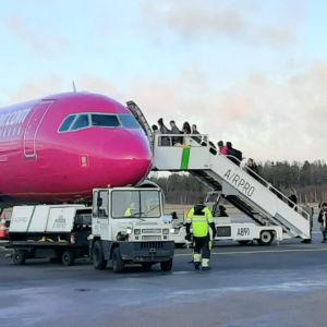 Passagerare går på ett flygfält fram till ett rosa-lilafärgat flygplan.