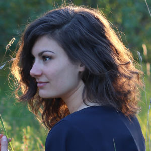 Rebecka Sretenovic sitter i en blå blus i gräset.