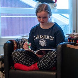 Kvinnlig gymnasieelev läser en lärobok i fysik i sitt rum