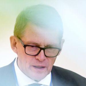 Matti Vanhanen i kostym och glasögon står och gestikulerar med händerna.