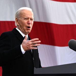 Joe Biden talar vid ett podium framför USA:s flagga.