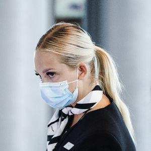 En Finnair-flygvärdinna i munskydd på Helsingfors-Vanda flygplats. Bakom henne en annan resenär i munskydd.
