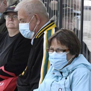 Passagerare iförda munskydd väntar på bussen.