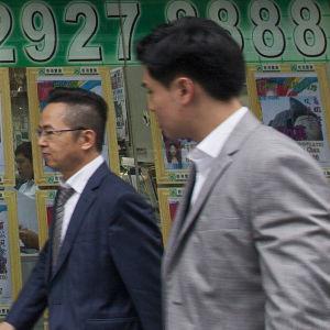 Två män framför en fastighetsförmedling i Hongkong.