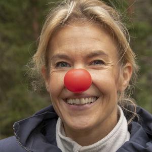 Puoli seitsemän -ohjelman juontaja Ella Kanninen sienimetsällä, Ellalla on punainen Nenäpäivä-nenä.
