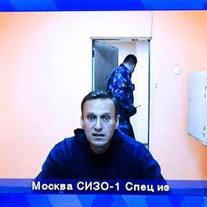 En medelålders man i blå kläder sitter vid en kamera och har en halvöppen dörr med en man i en uniform bakom sig.