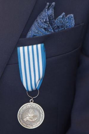En silverfärgad medalj i ett blåvitt band som är fäst vid bröstfickan på en kavaj.