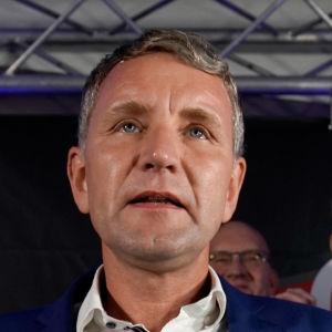 Björn Höcke i blå kostym står med en mikrofon i handen, två äldre män, också iklädda kostymer, står på vardera sida av Höcke och klappar.