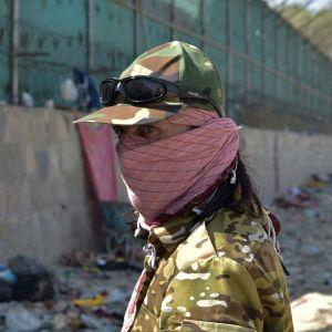 En talibankrigare tittar på förödelsen efter terrorattacken 26.8.2021 mot flygplatsen i Kabul