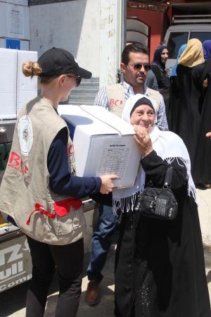 Mariette Hägglund delar ut en låda med förnödenheter till en kvinna i östra Mosul 2017.