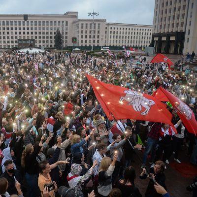 Suuri ihmismäärä seisoo neuvostotyylisten rakennusten ympäröimällä aukiolla. Monet pitävät ylhäällä puhelimiaan lamput sytytettyinä.