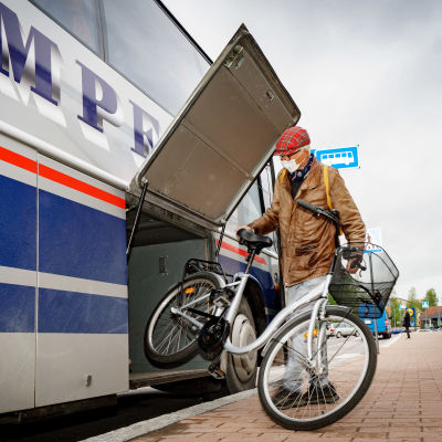 Mies nostaa polkupyöran bussin kyytiin.
