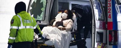 Kasvomaskiin puettu ja paareilla makaava nainen kannetaan ambulanssista sairaalan pihalle
