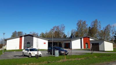 Fastighet i ett plan, fasad i vitt och rött. I förgrunden grön gräsmatta och bilar på parkeringsplats.