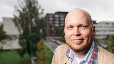 Kike Bertell står på en balkong i Västra Böle i Helsingfors