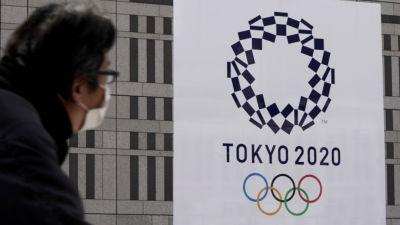 Person med ansiktsmask tittar på plakat med OS-logon.