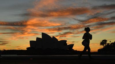 En kvinna springer utanför operahuset i Sydney.