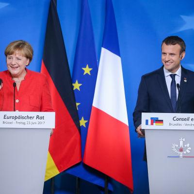 Tysklands förbundskansler Angela Merkel och Frankrikes president Emmanuel Macron ler bakom sina podium med Tysklands, EU:s och Frankrikes flagga i bakrgunden på EU-toppmötet.