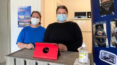 Två kvinnor med munskydd står bredvid varandra bakom en kassadisk.