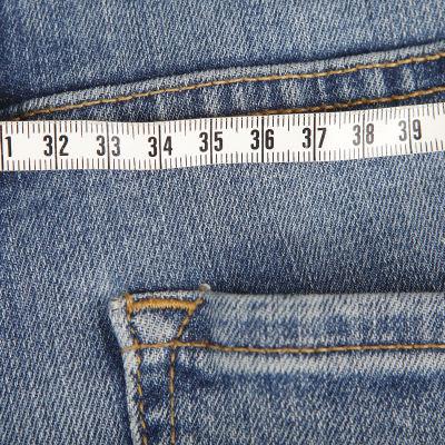 Närbild på ett par jeans med måttband ovanpå (illustrationsbild för övervikt).