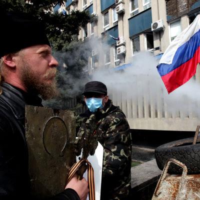 Ortodox präst utanför en ockuperad byggnad i Lugansk.