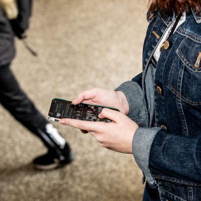 Nuori henkilö katsoo puhelintaan.