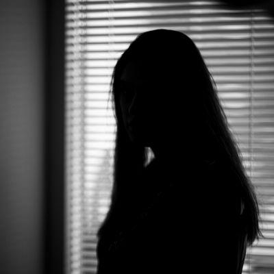 En svartvit bild på kvinna med långt hår vid ett fönster med spjälgardiner.