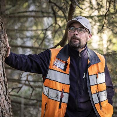 Ahti Räinä nojaa jykevään puuhun metsässä.