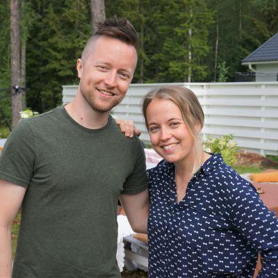 En man och en kvinna står på en gräsmatta.