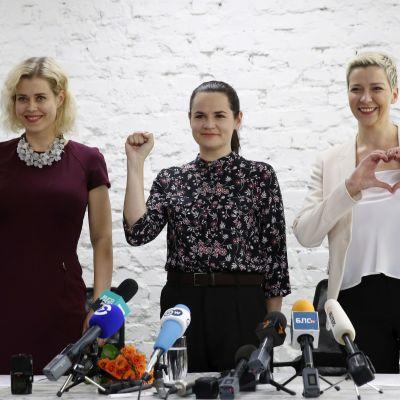 Kolme naista näyttää erilaisia käsimerkkejä: voitonmerkki, nyrkki ja sydän