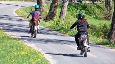 Mopedister kör efter varandra på en asfalterad väg.