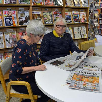Två kvinnor sitter och läser en tidning vid ett bord i ett bibliotek.