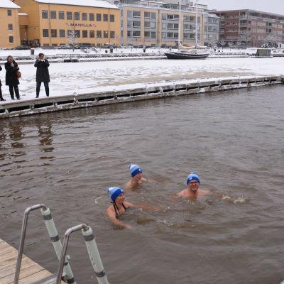 Tre personer simmar i en vak.