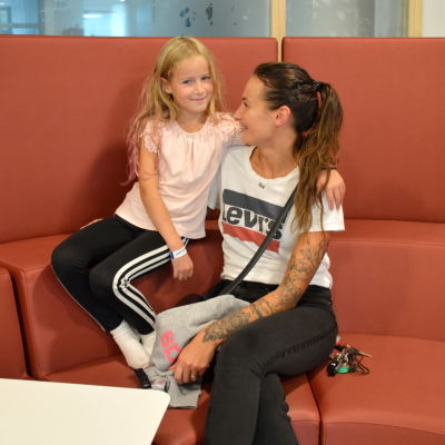 En mamma och en dotter sitter i en röd soffa och tittar på varandra.