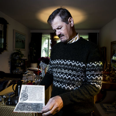 Veli Pekka Toropainen står i sitt vardagsrum och håller i en bok från 1600-talet.