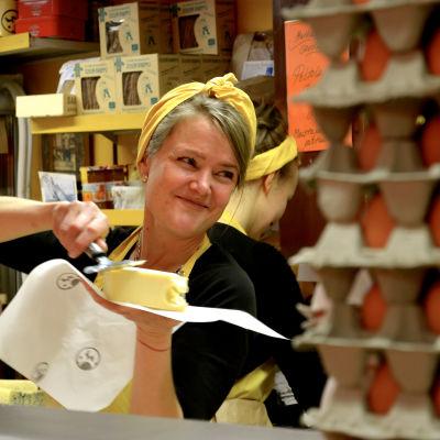 En kvinna i gult förkläde som håller i en ostbit.