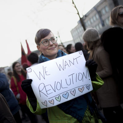 """En kvinna håller upp en skylt med texten """"We wan't revolution"""" på en demonstration i Berlin."""