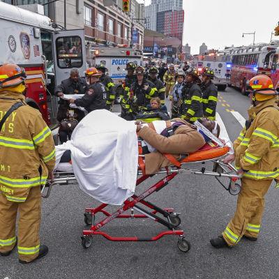 Räddningspersonal och -fordon utanför stationen Atlantic Terminal i New York efter en tågolycka där över 100 människor kommit till skada. I mitten av bilden ligger en man på bår.