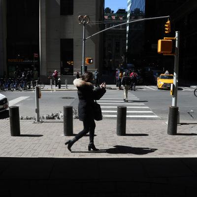Fotgängare går förbi säkerhetshinder på en trottoar på Wall street, New York.