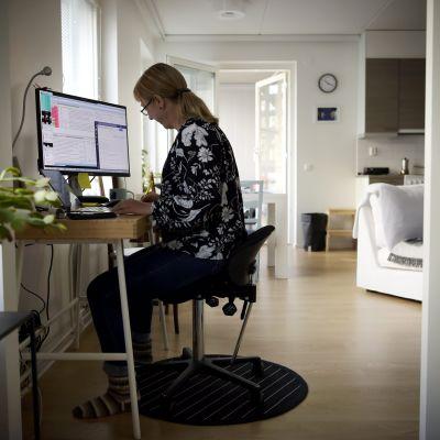 Kvinna jobbar vid dator i sitt hem