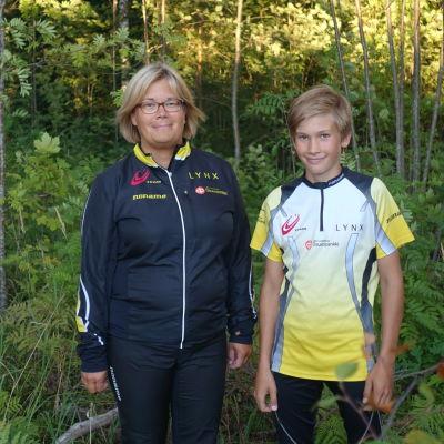 En kvinna och en pojke står bredvid varandra i en grön lummig skog. De ler och har på sig träningskläder. De har båda blont hår och kvinnan har glasögon.