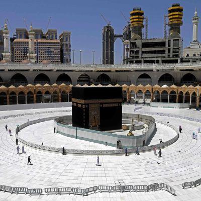 Några muslimer går runt byggnaden Kaba i Mekka i Saudiarabien.