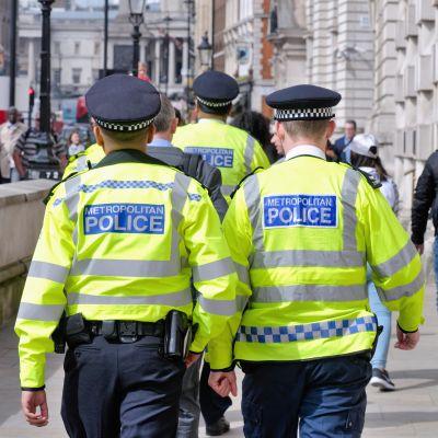 Två poliser går i London. Deras ryggar är mot kameran.