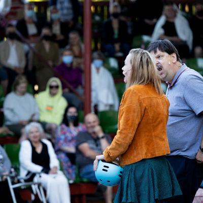 Etualalla lavalla seisoo mies ja nainen. Mies katsoo naista vihaisesti ja nainen näyttää järkyttyneeltä. Taustalla yleisö katselee.