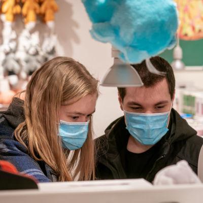 En ung kvinna och en ung man tittar på varor i en affär.